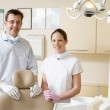 Dentist and assistant in exam room smiling — Stock Photo #4769374