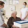 Dentist and assistant in exam room with woman in chair smiling — Stock Photo