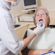 Dentist in exam room with woman in chair — Stock Photo
