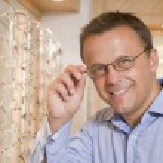 Man trying on eyeglasses at optometrists smiling — Stock Photo