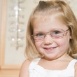 Young girl trying on eyeglasses at optometrists smiling — Stock Photo