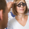 Optometrist in exam room with woman in chair — Stock Photo