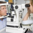 Optometrist in exam room with man in chair — Stock Photo