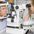 Stock Photo: Optometrist in exam room with min chair