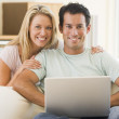 Couple in living room using laptop smiling — Stock Photo