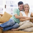 Couple in living room with remote control smiling — Stok fotoğraf