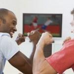 zwei männer im wohnzimmer vor dem fernseher und jubeln — Stockfoto