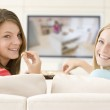 Two women in living room watching television eating chocolates s — Stock Photo