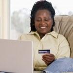 mulher na sala usando laptop, segurando o cartão de crédito e coordenador — Foto Stock