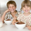 Two young children in kitchen eating cereal smiling — Stock Photo