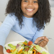Young girl in kitchen eating salad smiling — Stockfoto