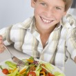 Young boy in kitchen eating salad smiling — Foto de Stock