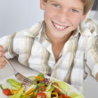 Young boy in kitchen eating salad smiling — ストック写真
