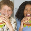 Two young children in kitchen eating cheeseburgers smiling — Stock Photo #4769853