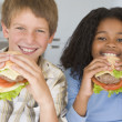 Two young children in kitchen eating cheeseburgers smiling — Stock Photo