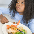 Young girl in kitchen eating chicken and vegetables — Stock Photo