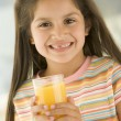 Young girl indoors drinking orange juice smiling — Stock Photo
