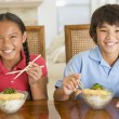 Two young children eating chinese food in dining room smiling — Stock Photo #4769888