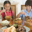 Two young children eating chinese food in dining room smiling — Stock Photo