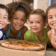 Four young children indoors eating pizza smiling — Stock Photo #4769925