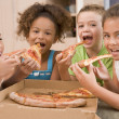 Four young children indoors eating pizza smiling — Stock Photo