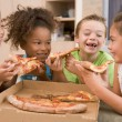 Four young children indoors eating pizza smiling — Stock Photo #4769928