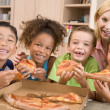 Four young children indoors with woman eating pizza smiling — Stock Photo