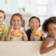 Four young children eating cheeseburgers in living room smiling — Stock Photo