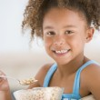 Young girl eating cereal in living room smiling — Stock Photo