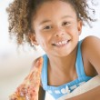 Stock Photo: Young girl eating pizza slice in living room smiling