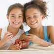 Two young girls eating strawberries in living room smiling — Stock Photo #4769971