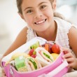 young girl holding lunchpaket in living room smiling — Stockfoto