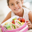 Young girl holding packed lunch in living room smiling — Stockfoto