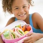 jong meisje houden Lunchpakket in woonkamer glimlachen — Stockfoto