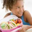 Young girl holding packed lunch in living room smiling — Stock Photo #4769985