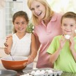 Woman and two children in kitchen baking and smiling — Stock Photo #4769990