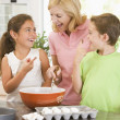 Woman and two children in kitchen baking and smiling — Stock Photo