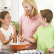 Woman and two children in kitchen baking and smiling — Stock Photo #4769992