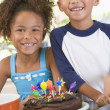 Two children in kitchen with birthday cake smiling — Stock Photo