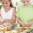 Two children in kitchen decorating cookies smiling — Stock Photo #4769999