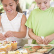 Two children in kitchen decorating cookies smiling — Stock Photo