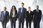 Group of business walking towards camera — Stock Photo