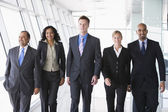 Group of business walking towards camera — Stock Photo