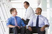 Group of businessmen talking in lobby — Stock Photo