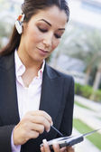 Businesswoman using PDA and earpiece — Stock Photo