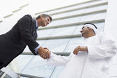 A Middle Eastern businessman and Caucasian man shaking hands out — Stock Photo