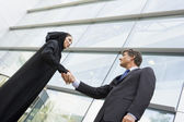A Middle Eastern businesswoman and a Caucasian man shaking hands — Stock Photo