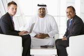 Two Middle Eastern men and a caucasian man talking at a business — Stock Photo