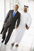 Two Middle Eastern businessmen walking in a corridor — Stock Photo