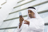 A Middle Eastern businessman using a PDA — Stock Photo
